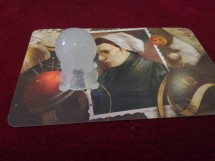 Mysterium Review: A murderer card. Note how there is not just a person but a load of items around her.